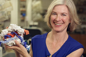 Jennifer Doudna holds a model of the CRISPR-Cas9 protein (white) interacting with DNA (orange and blue).